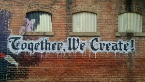 "Brick wall with ""Together we create"" painted on it."